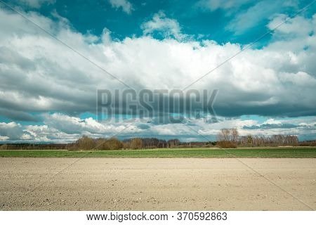 Spectacular Clouds On The Sky, Plowed Field And Forest On The Horizon, Spring View