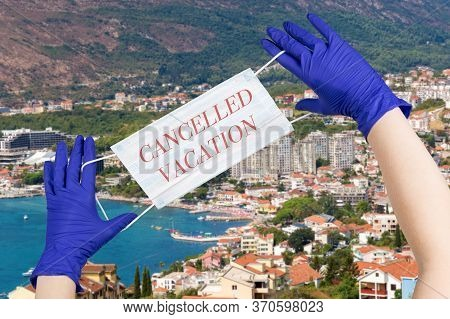 Woman Hands With Latex Gloves On Them Are Holding Safety Mask With Sign Cancelled Vacation Against M