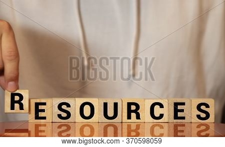 Businessman Protecting His Resources Holding His Hands Above A Row Of Wooden Blocks With The Word -