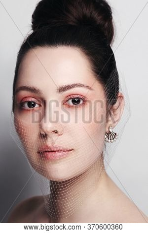 Vintage style portrait of young beautiful woman with pink makeup and fishnet mask on her face