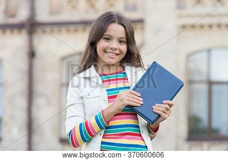 Required School Reading List. Happy Child Hold Book Outdoors. School Library. Little Girl Back To Sc