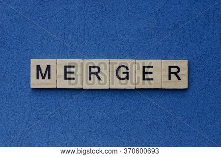 Text On Gray Word Merger In Small Wooden Letters With Black Font On A Blue Background