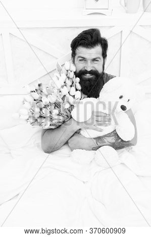 Teddy Bear. Fresh Flowers. Bearded Hipster In Bed. Valentines Day Gift. Birthday Holiday. Man Hold T