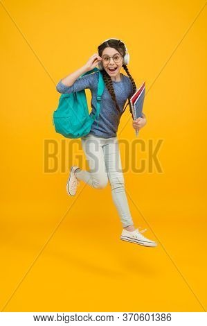 Unassailable Childhood. Happy Child In Midair Yellow Background. Little Girl Back To School. School