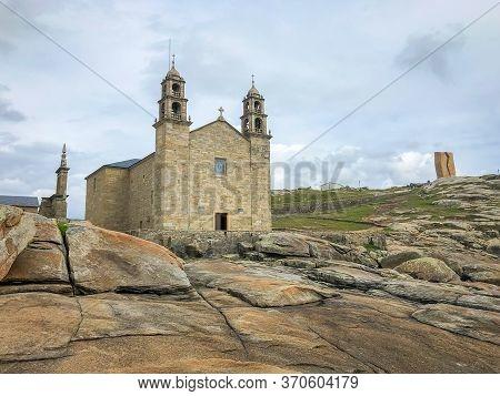 Nosa Senora Of Barca Church On The Ancient Sacral Stones Of Rocky Cape. Beach In Muxia, Galicia, Spa