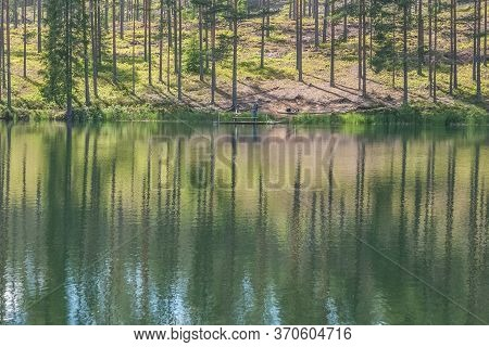Cloudy Sky And Tree Reflection In Secluded Area By The Lake. Calm Waters And Cloudy Sky. Fisherman I