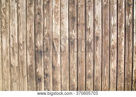 The Background Of The Fence Is Made Of Old Planed Dark Boards With A Pronounced Wood Structure Locat