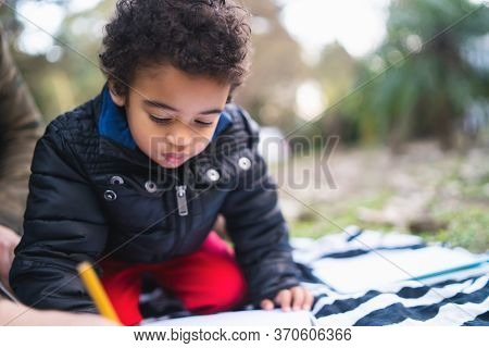 Portrait Of Cute African American Little Boy Having Fun And Playing Outdoors In The Park.