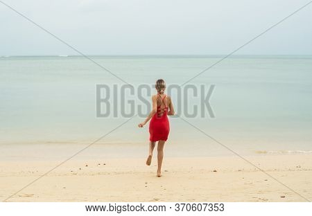 Young Woman In A Red Dress Runs And Jumps On A White Sand Beach Into Tropical Sea. Young Happy Woman