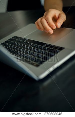 Closeup shot of caucasian male hand on touchpad of modern laptop