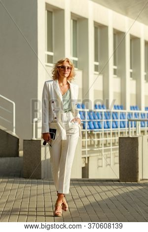 Full-lenght portrait of young attractive businesswoman wearing white suit walking on the street confidently on a sunny day. Model holding tablet. cellphone and car keys in her hands.
