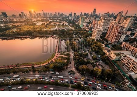 Benjakiti Public Park With A Lake, Skyscrapers And Traffic In Bangkok, Thailand At Sunset
