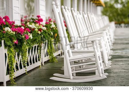 Several White Rocking Chairs On Long Porch Just Waiting For You To Come And Enjoy On A Luxury Trip T