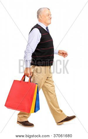 Full length portrait of a mature man coming back after shopping isolated on white background