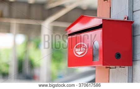 Red Mail Box Or Post Box Set Up On The Wooden Wall For Sending And Receiving The Mails And Parcels.