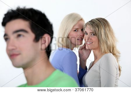Two girls gossiping about man