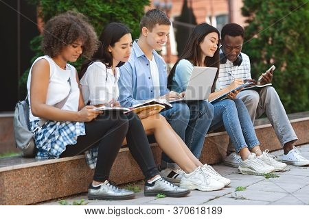Diverse Teen Friends Studying Together In University Courtyard, Preparing For Exams Outdoors, Having