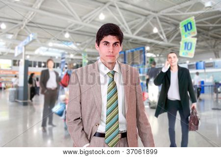 Young successful businessman smiling and looking at camera in a modern airport