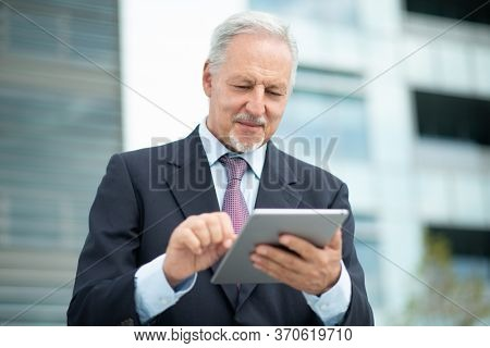 Business man looking at his tablet outdoor in front of his office
