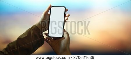 Female Content Creator Looking Image On Camera While Sitting At Wooden Worktable