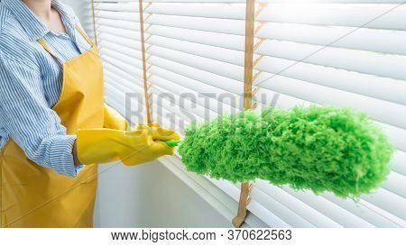Young Female Spring Cleaning House Interior Holding A Duster For Wiping Dust Dusting Furniture At Ho