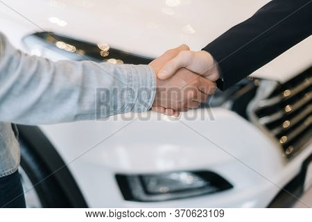 Buyer Of Car Shaking Hands With Seller In Auto Dealership, In Front Of Car. Close-up Of Handshake Of