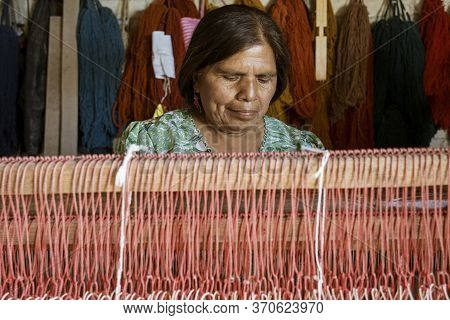 Oaxaca, Mexico - 2019-11-30 - Woman Works At Her Loom Making A New Blanket.