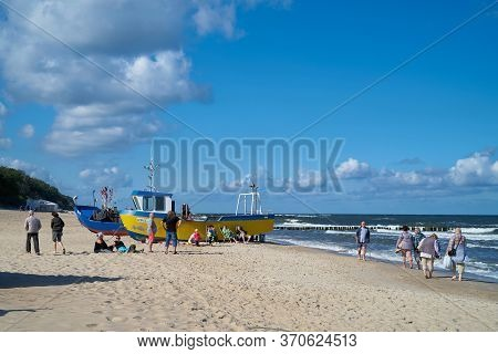 Rewal, Poland - September 05, 2019: Holidaymakers And Fishing Boats On The Beach Of Rewal On The Pol