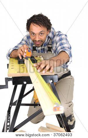 Carpenter carefully measuring plank of wood