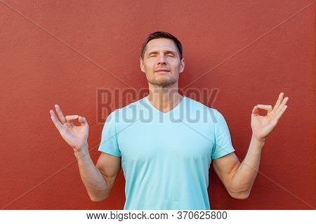 Man Feeling Relaxed, Joyful Calm. Handsome Guy Holding Hands Zen Mudra Gesture Nirvana Meditation Do