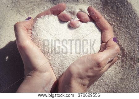 Top View On Beautiful Woman's Hands In The Shape Of A Heart With Sand. Symbol Of Love.