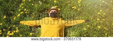 Old Man In Yellow Hoodie And Black Mask Lies With Outstretching Arms Among Dandelions In Spring Gard