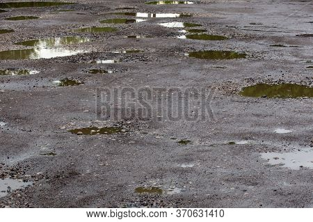 Bumpy Damaged Road Asphalt With Multiple Puddles After Rain At Summer Daytime