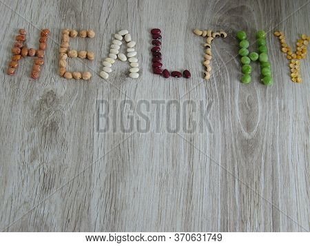 Healthy Word Written On Board With Types Of Beans. Written Appearance Healthy On Wooden Background.