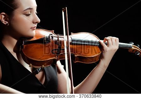 Female Musician Playing Symphony On Violin Isolated On Black