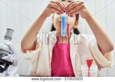 Image Of Little Girl Looking At Two Flasks Containing Red And Blue Liquids To Perform Experiments In