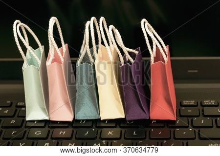 Row Colorful Paper Shopping Bags With Mobile Phone On A Laptop Keyboard. Ideas About Online Shopping