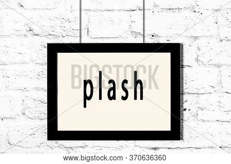Black Wooden Frame With Inscription Plash Hanging On White Brick Wall
