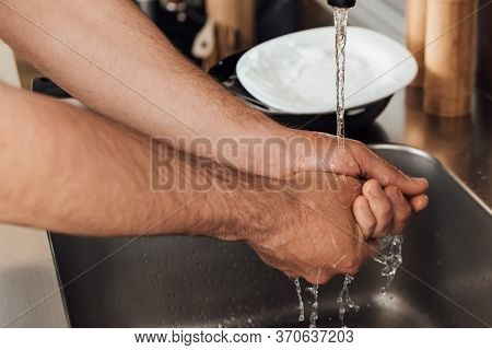 View Of Man Washing Hands Near Tableware On Worktop In Kitchen