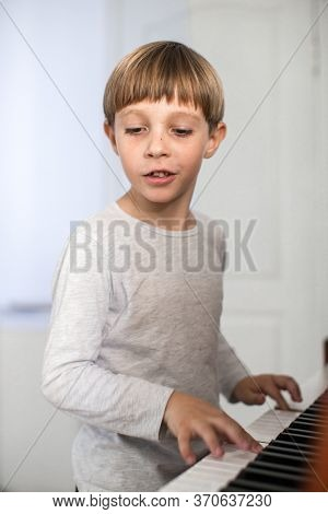little boy plays the piano
