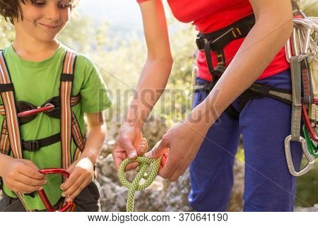 The Mother Teaches The Child To Tie A Safety Knot For Climbing, Protective Equipment For Climbing An