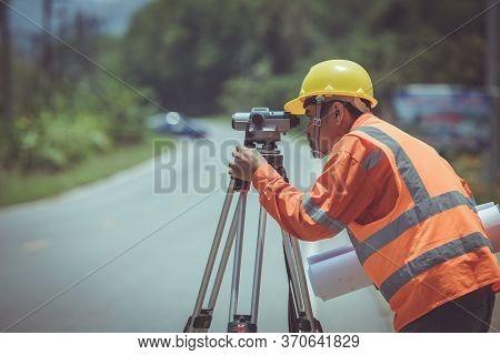 Surveyor Engineers Work On Road Construction Site