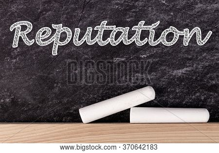 Reputation Text On Blackboard With Two Pieces Of Chalk.