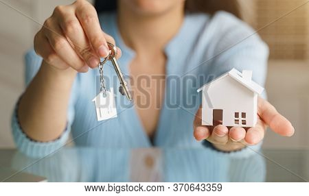 Woman Holding White House Model And House Key In Hand.mortgage Loan Approval Home Loan And Insurance