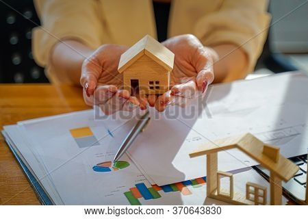 Close Up Of Home Agents Holding House Or Home Model  In Hand,real Estate And Property Concept.