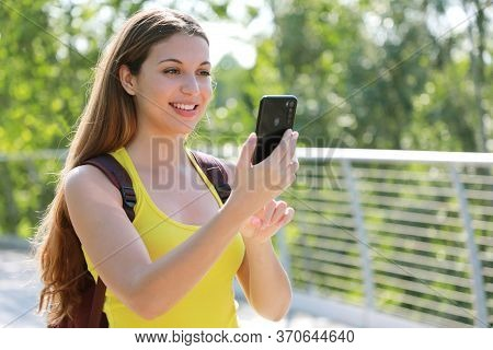 Portrait Of Smiling Female Hiker Checking Gps Coordinates With Her Smart Phone Looking For The Right