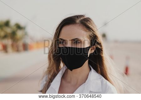 Portrait Of A Young Woman Wearing Black Protective Face Mask. Reusable Mask. Dust Protection. Covid