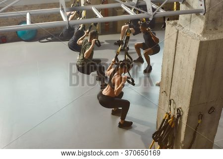 Group Of Sportive People Doing Fitness Trx Training Exercises At Industrial Gym. Push-up, Group Work