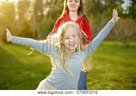 Two Cute Sisters Fooling Around Together On The Grass On A Sunny Summer Day. Children Being Silly An