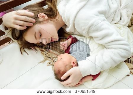 Cute Big Sister Admiring Her Newborn Brother. Adorable Teenage Girl Holding Her New Baby Boy Brother